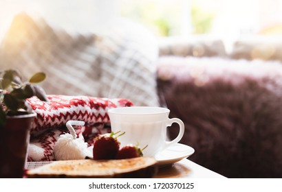 Still life Hot cuppa tea with steam with blurry foreground of toasted on a coffee table with morning light or Can be Cozy scene of relaxing in afternoon tea with bread in sunny day autumn or winter