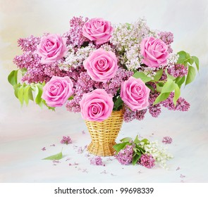 Still life with huge bunch of roses, lilac  flowers and lily of the valley flowers on painting background