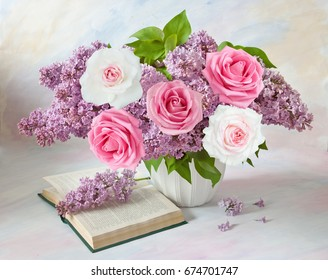 Still life with huge lilac flower and roses bunch with open book on artistic background