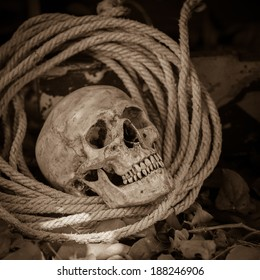 Still life with human skull with old rope on ground floor