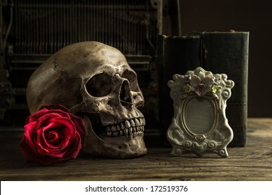 Still life with human skull with red rose, old book and telephone on wooden floor