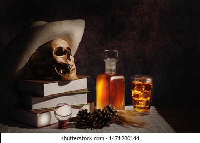 still life of humen skull with a glass and a bottle of whisky on table with white cloth cover for holloween night