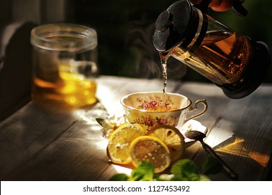 Still life image of cup of herbal tea with fresh green mint ,honey and lemon on wooden background.Man poring hot tea with vapor and steam in a cup.Light shining up on the scene.Quiet,peace and relax.
