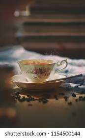 Still life image of cup of tea with  spilled tea leaf on wooden table.Man poring hot tea with vapor and steam in a cup. . Sunlight shining upon the cup.Light and shade of evening.Quiet,peace and relax