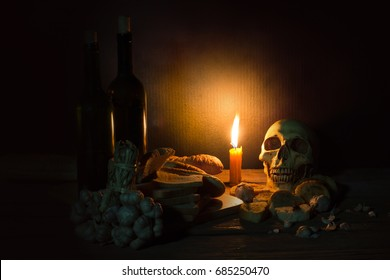 Still Life Image and dim light/yellow lit candle with bundle of garlic bulbs and rotten breads as foreground