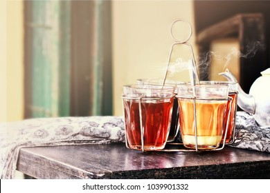 Still life image of a hot milk tea with vapor and steam on old wooden table.Traditional tea can be found in the Southeast Asian countries.Southern Thailand and Malay style.Vintage and classy