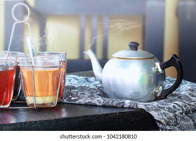 Still life image of a hot milk tea pot with vapor and steam on old wooden table.Traditional tea can be found in the Southeast Asian countries.Southern Thailand and Malay style.Vintage and classy