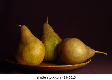 Still life image of pears with dark background