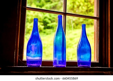 A still life image of three old cobalt blue glass bottles that are illuminated through a window.