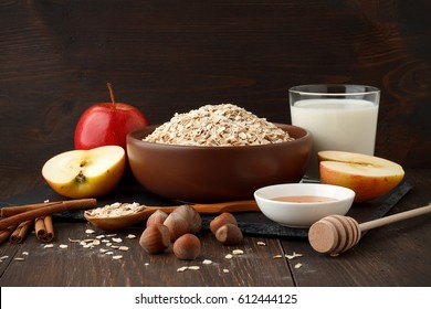 Still life of ingredients for healthy breakfast: rolled oat flakes, milk, apple, honey, hazelnut, cinnamon. Concept of healthy diet.