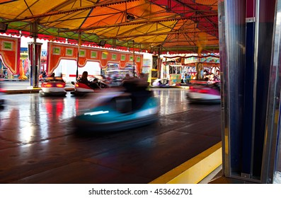 Still life intense view of fun park bumper cars ride under colorful marquee, sunny day. Active bumper cars motion blur entertainment in fun amusement park, funfair rides moving fast, bright lights.