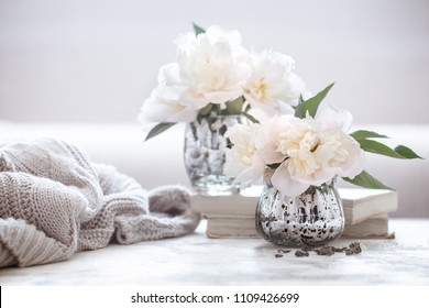 still life with interior details and flowers with peonies in the living room, the concept of home comfort and interior