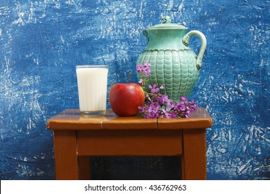 Still life. A jug and a glass of milk, an apple and a bouquet of wildflowers, on a blue background