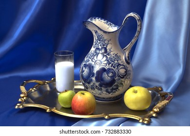 Still life of a jug in the style of Gzhel, a glass of milk and fruit that are installed on the tray against the blue silk.