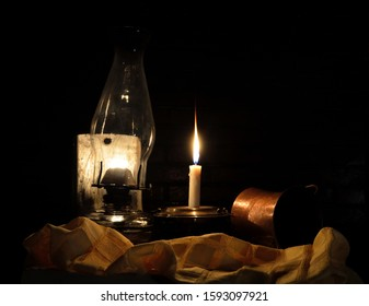 Still life with kerosene lamp and lit candle next to copper bowl and cloth