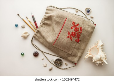 Still life with kids backpack and seashells. Handmade kids backpack with embroidery red ornament. Made of linen fabric. Top view travel or vacation concept. Nautical theme. White background