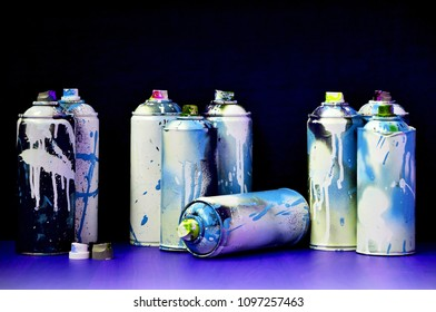 Still life with a large number of used colorful spray cans of aerosol paint lying on the treated wooden surface in the artist's graffiti workshop. Dirty and stained cans for spray art