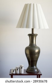 Still life of a large table lamp and matching porcelain containers on a small table.