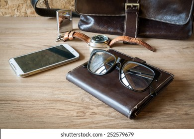 still life with leather bag, watch , lighter , glasses and smartphone on wood background