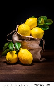 still life of lemons with green leaves on wood and burlap sack