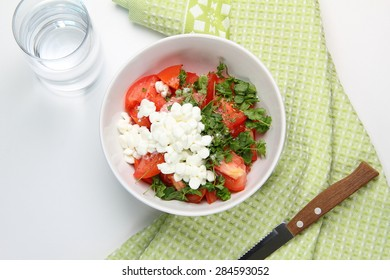 still life of lettuce with fresh tomatoes, parsley, basil, onion, with a handful of granulated cottage cheese in white dish, standing on a green towel, a glass of water and a knife