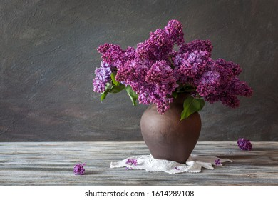 Still life. Lilac Bouquet in a clay jug on a wooden table. Rustic style.