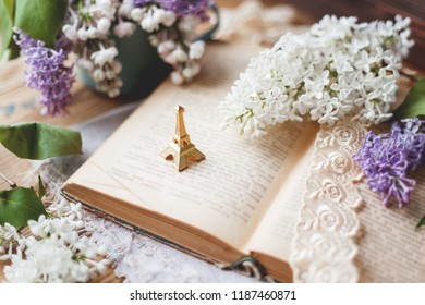 Still life with lilac flowers, book, lace bookmark and miniture Eiffel tower. Rustic vintage background. Interesting reading about France.