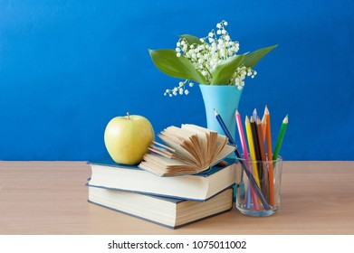 still life with lily of the valley and book pile and apple. Teacher's day concept