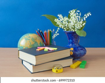 Still life with lily of the valley bunch, book and globe. Teacher's day concept