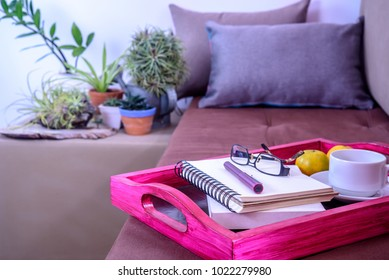 Still life of Living room with book, eyeglasses, coffee cup on rustic wooden tray on sofa / Home decoration & lifestyle concept