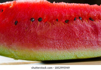 still life macro photography watermelon slice with seeds on a cutting board with rim light and in a black background