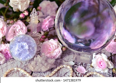 Still life with magic crystal ball, pink roses and necklace.  Esoteric, wicca and occult background, fortune telling and divination ritual with tarot cards.