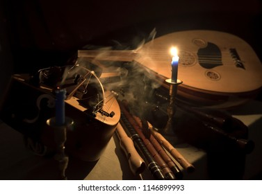 Still life with medieval musical instruments, lute, flutes, hurdy-gurdy and tambourines candles and smoke