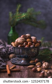 Still life of a metal bowl full of various nuts - almonds, hazelnuts, brazil nuts and walnuts. Next to bowl are cinnamon sticks and more nuts, and there is a green spruce branch in the background.