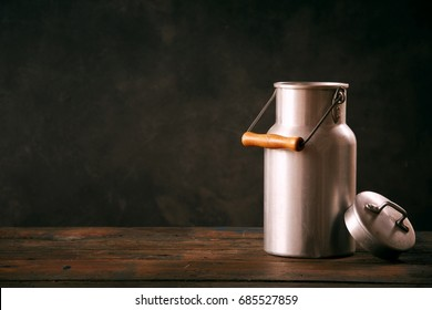 Still life with metal vintage milk can standing on wooden countertop