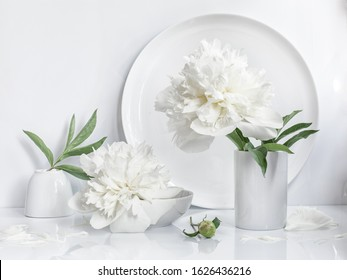 Still life in a minimalist white color scheme. One white peony flower in a vase against a white circle, 2 bowls with a peony leaf.
