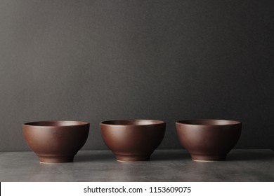 still life minimalistic  composition of  three brown bowls in row on the darck background with copy space