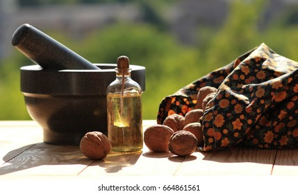 Still life of a mortar, scattered walnuts and a bottle of oil against blurred green background, sunlit