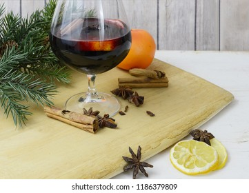 Still life of mulled wine with ingredients scattered about on rusting wooden table top. Includes citrus, cinnamon, and star anis. Includes an orange and some seasonal evergreen.
