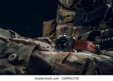 Still life with nice watch and military uniform with typical camo pattern and gun.