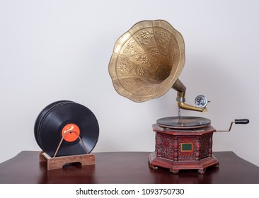 Still life of a nineteenth century phonograph (gramophone) and vinyl records on a wooden table and beige wall