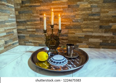 Still life with objects Judaica. Beautiful candlestick with burning candles, a silver glass for blessing and a white yarmulke. Background stone wall. Concept of artistic photography