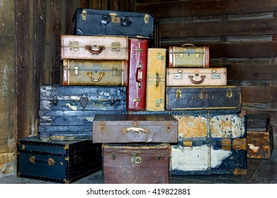 Still life of old antique suitcases stacked up high in a station.