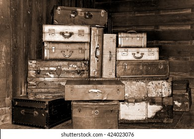 Still life of old antique suitcases stacked up high in sepia.