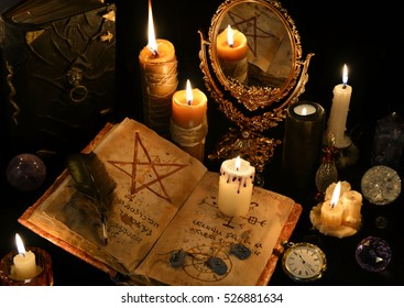 Still life with old book, ancient runes and mirror in candle light. Halloween and occult concept, black magic ritual. There is no foreign text in the image, all symbols are imaginary and fantasy ones