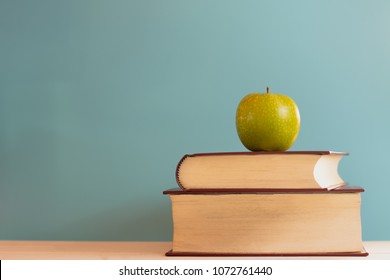 still life of old books stack  and   green apple on the desk,table with light green background.