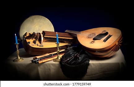Still life with old medieval instruments hurdy gurdy flutes bagpipe lute and tambourine in dark light with candles and candlestick