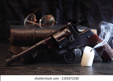 Still life with old revolver near book and extinguished candle