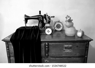 Still life with an old sewing machine, a clock, a ceramic vase with a flower and an apple.