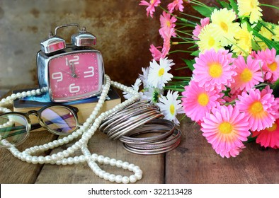 Still life with old telephone, glasses, artificial flower, bracelet and necklace on wooden table